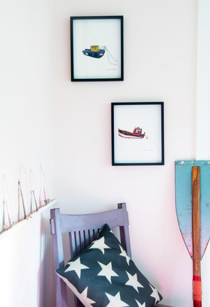 Two embroidered tugboat pictures with a row of scenes in arches on the shelf