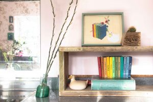photograph of picture sat on top of observer books and duck that are in embroidered picture
