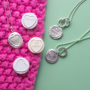 Kiss and Be happy love heart pendants laid on pink and green.