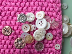 Three button rings in silver and copper clay sat with a pile of buttons.