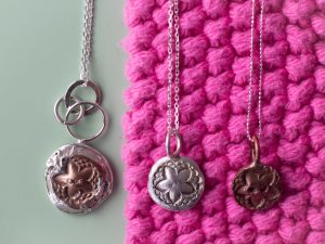 Reversible button pendant with two other button pendants.