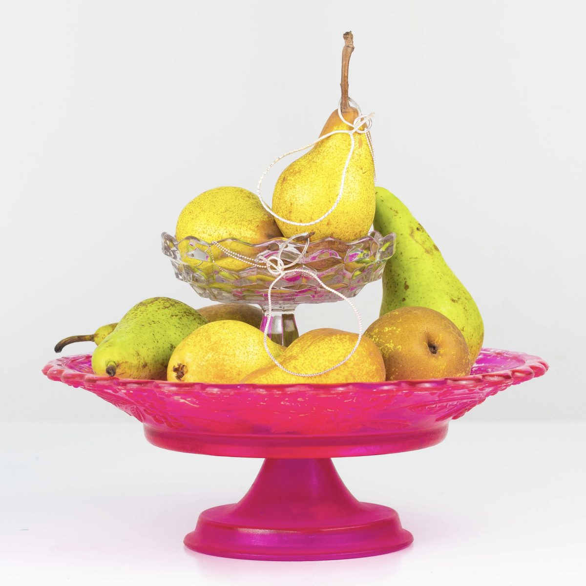 silver pear necklaces sat on a pile of pears on a pink cake stand