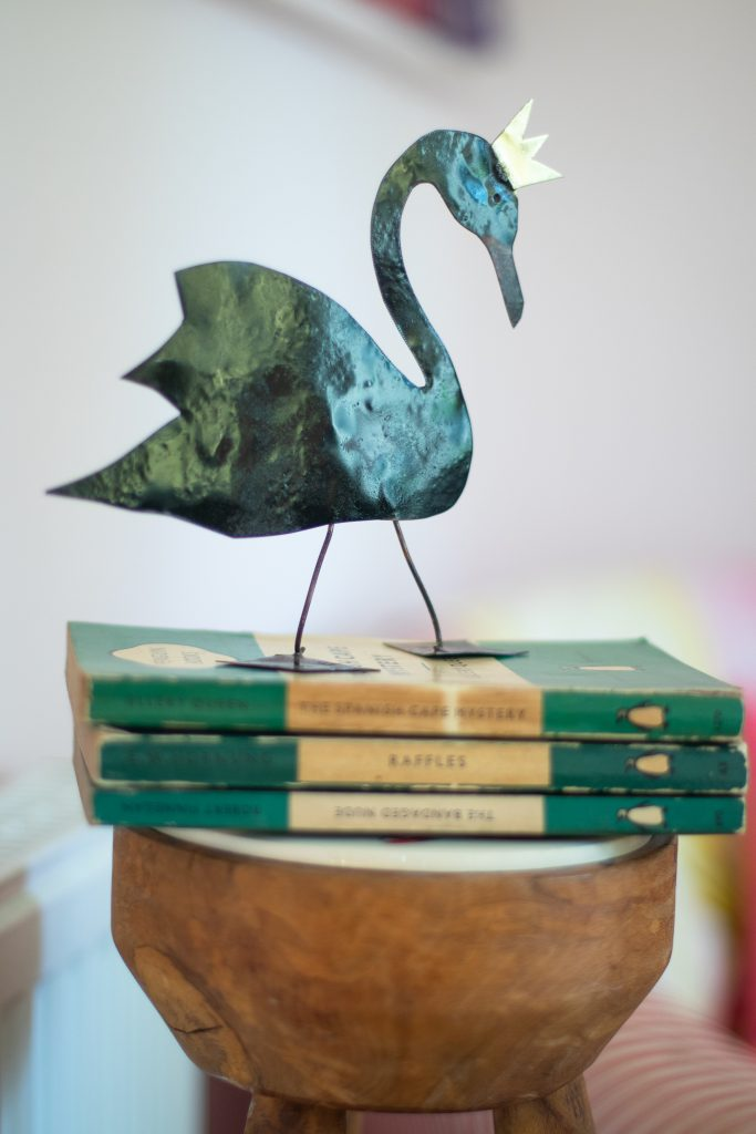 copper black sprayed swan in a crown sat on a pile of penguin books