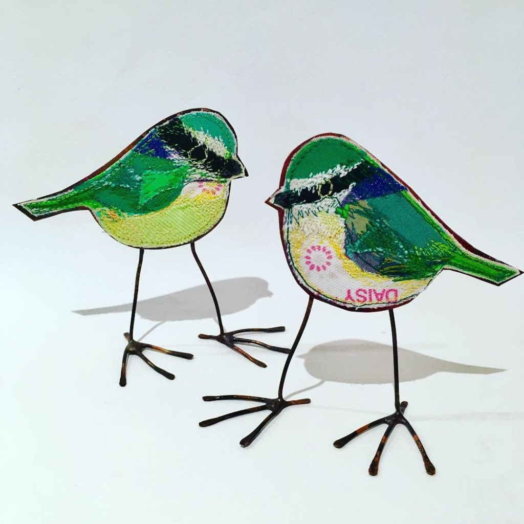Two greeny blue tit embroidered birds with copper bodies.
