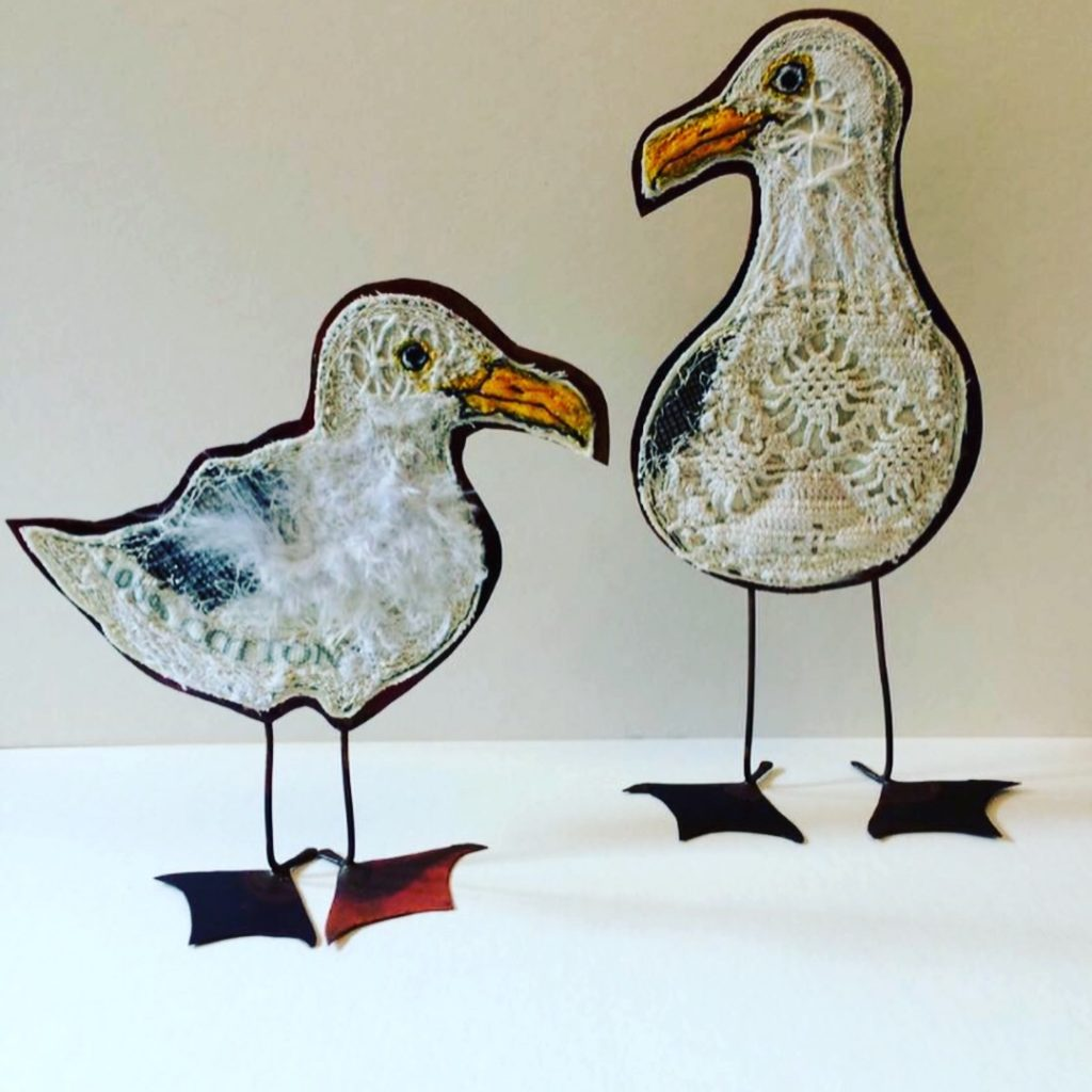 Two embroidered seagulls with copper bodies