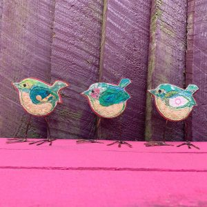 Three green wrens on a pink table by a purple fence