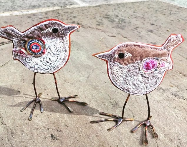 Two embroidered wrens with copper bodies